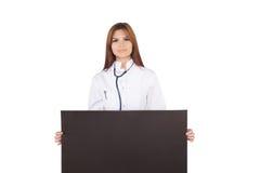 兴高采烈的女性医生画象,拿着黑卡片 免版税图库摄影