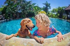 兴高采烈的妇女滑稽的画象有狗的在游泳池 免版税库存照片