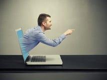 兴高采烈的英俊的人离开膝上型计算机 图库摄影