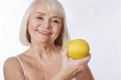 兴高采烈的资深妇女饮用苹果在她的手 图库摄影