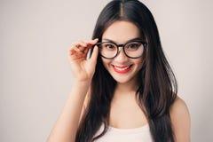 戴兴高采烈的面孔佩带的眼镜的年轻美丽的亚裔妇女 库存照片