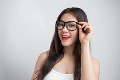 戴兴高采烈的面孔佩带的眼镜的年轻美丽的亚裔妇女 图库摄影
