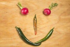 在萝卜和胡椒外面的兴高采烈的面孔 库存图片