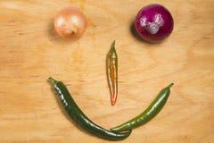在葱和胡椒外面的兴高采烈的面孔 免版税图库摄影