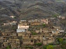 高阿特拉斯山脉的一个传统巴巴里人村庄:有屋顶平台的小黏土褐色房子在山坡,摩洛哥 库存图片