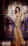高雅。黄色礼服的迷人的光彩的夫人。正式党 免版税库存照片