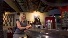 高雅孤独的妇女在酒吧柜台附近喝酒 影视素材