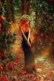 高雅摆在有蛇麻草花圈的森林里的秀丽夫人在头的 免版税库存照片