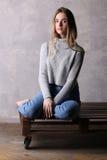 高领衫的女孩坐委员会 灰色背景 免版税图库摄影