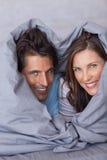 高兴夫妇获得被包裹的乐趣在他们的鸭绒垫子 免版税库存图片