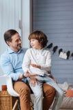 高兴幼儿坐他的父亲膝盖 库存照片