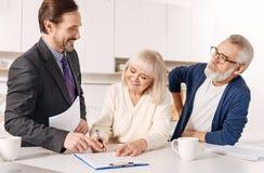 高兴房地产开发商与顾客一起使用年长夫妇  库存图片