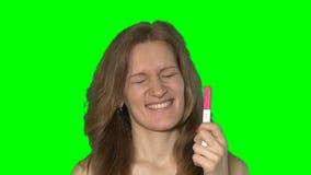 高兴的疯狂的有吸引力的与巨大的微笑的妇女展示正面怀孕的测试在面孔 股票视频