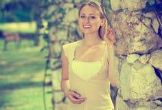 高兴的年轻白肤金发的妇女画象在庭院里 免版税库存图片