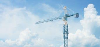 高建筑用起重机站立反对多云天空 图库摄影