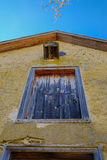 高黄色涂了灰泥与五颜六色的窗口r的殖民地结构 免版税库存照片