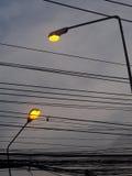 高黄色电灯泡照明设备街灯室外剪影隔绝与灰色黑暗的多云天空 免版税库存照片