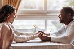 高兴非裔美国人的夫妇有交谈在咖啡馆 免版税图库摄影