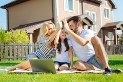 高fiving快乐的年轻的家庭在野餐 库存照片
