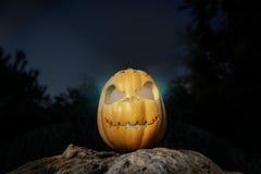 鬼的万圣夜温暖的霓虹南瓜在一个岩石在黑暗中 免版税库存照片