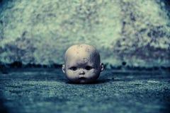 鬼的玩偶头在被困扰的房子里 库存图片
