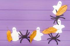 鬼魂和蜘蛛不同的纸剪影与秋叶由万圣夜角落框架制成 免版税图库摄影