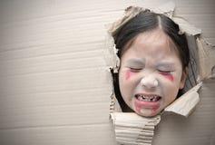 鬼魂孩子哀伤和通过在纸板的孔 图库摄影