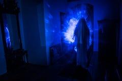 鬼魂恐怖剪影在暗室里面的有巫婆镜子可怕万圣节概念剪影的在鬼屋里面的有雾的 免版税库存图片