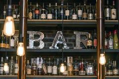魁北克加拿大13 09 2017 - 苦味健胃药和酒禁止逆与瓶被定调子的葡萄酒样式砖墙和四周光 免版税库存图片