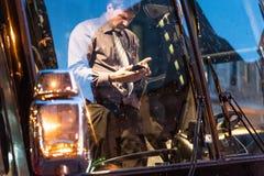 魁北克市,加拿大- 2018年5月21日:使用他的智能手机的公交司机 库存图片