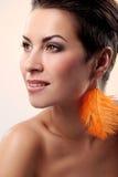 魅力和华美的浅黑肤色的男人有羽毛耳环的 免版税库存图片