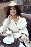 魅力女孩穿有典雅的帽子的豪华米黄外套 免版税库存图片