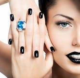 魅力妇女的钉子、嘴唇和眼睛绘了颜色黑色。 免版税库存照片