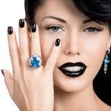 魅力妇女的钉子、嘴唇和眼睛绘了颜色黑色 免版税库存图片