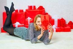 魅力庆祝 圣诞节时尚 拿着红色当前箱子的微笑的美丽的少女 性感的圣诞老人妇女 免版税库存照片