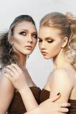 魅力构成有长的发型的两名妇女坐街道围住在黑暗的背景 时尚颜色画象,被修饰的照片 免版税库存图片