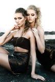 魅力构成有长的发型的两名妇女坐街道围住在黑暗的背景 时尚颜色画象,被修饰的照片 库存图片