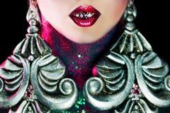 魅力的病残 有明亮的构成和巨大的耳环的女孩 宝石或首饰在嘴 Cncept 免版税库存图片