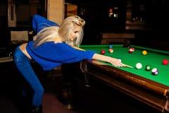 魅力美丽的白肤金发的妇女演奏台球 免版税库存图片