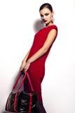 魅力美好的性感的时髦的深色的白种人少妇模型特写镜头画象在红色礼服的有黑b的 免版税库存图片
