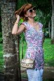 魅力肉欲的年轻时髦的夫人室外时尚画象太阳镜的有豪华手工制造snakeskin Python袋子的 免版税库存图片
