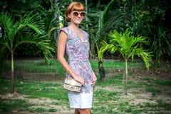 魅力肉欲的年轻时髦的夫人室外时尚画象太阳镜的有豪华手工制造snakeskin Python袋子的 库存照片