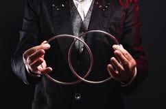 魔术师与金属圆环的展示把戏 与支柱的操作 库存图片