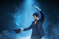 魔术师或魔术师显示魔术技巧 蓝色阶段光在背景中 库存图片