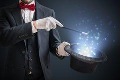 魔术师或魔术师显示魔术技巧 蓝色阶段光在背景中 免版税图库摄影