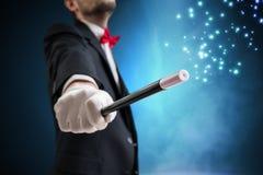 魔术师或魔术师显示魔术技巧 蓝色阶段光在背景中 免版税库存照片