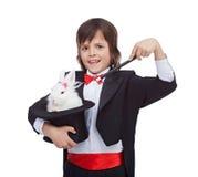 年轻魔术师男孩用在他不可思议的帽子的逗人喜爱的兔子 免版税库存图片