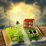 魔术打开了与用草树扔石头的方式盖的房子的书 免版税图库摄影
