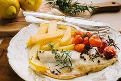 鱼内圆角用土豆,西红柿 库存图片
