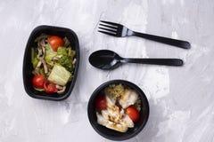 鱼和海鲜、亚洲膳食在eco食盒有匙子的和叉子在灰色桌,顶视图上 免版税库存图片